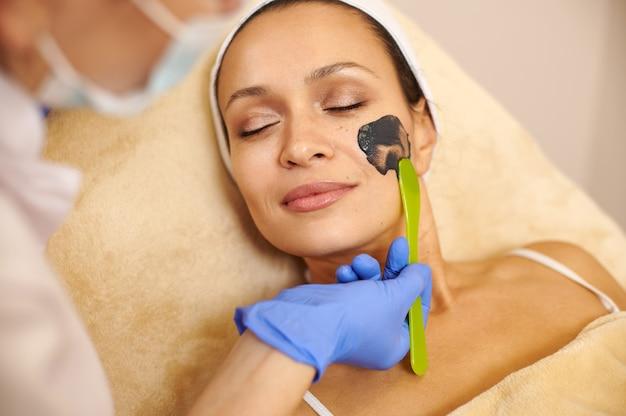 Крупным планом лицо красивой женщины и руки эстетика, наносящие черный косметический продукт на ее лицо