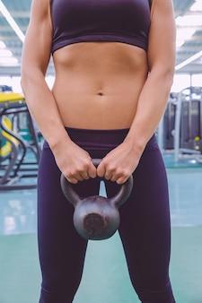 Крупным планом красивая женщина с тонкой талией и черной спортивной одеждой держит черную железную гирю в фитнес-центре