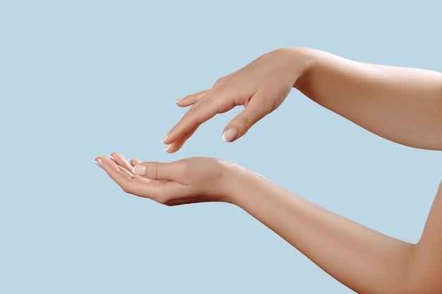 손톱에 프랑스 매니큐어와 아름 다운 여자 손의 근접 촬영은 파란색 배경에 격리, 크림을 적용, 마사지. 손 피부 관리.