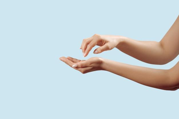 손톱에 프랑스 매니큐어를 바르고 아름다운 여성의 손을 닫고 파란색 배경에 크림을 바르고 마사지를 합니다. 손 피부 관리.