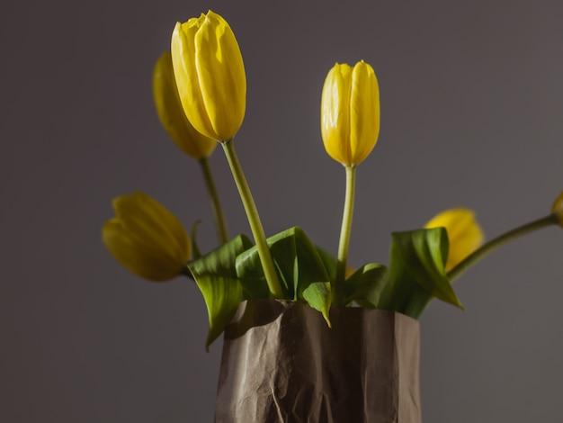Крупный план красивых желтых тюльпанов в бумажной сумке