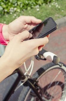 화창한 여름날 그녀의 스마트폰을 보고 있는 맞춤형 픽시 자전거를 가진 아름다운 젊은 낚시를 좋아하는 여성의 클로즈업. 부드럽고 따뜻한 음색.