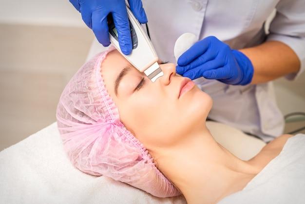美容院で超音波装置で超音波顔の角質除去とキャビテーション顔の剥離を受けている美しい若い女性のクローズアップ。