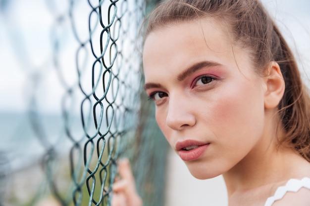 チェーンリンクフェンスの近くに立っている美しい若い女性のクローズアップ