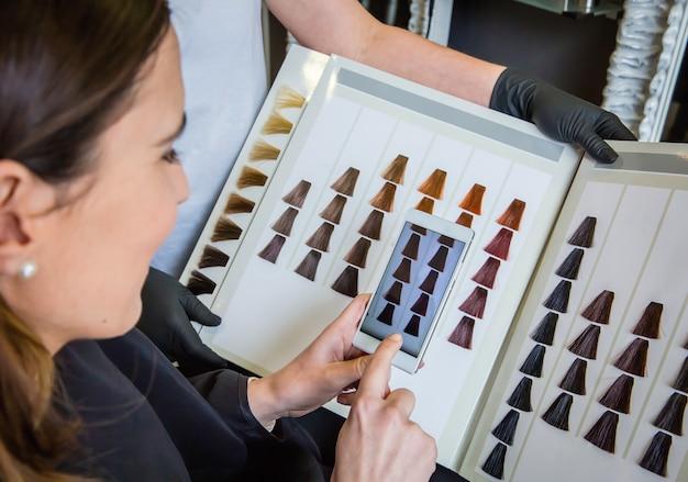 스마트폰으로 머리 염색 팔레트에 사진을 찍는 아름다운 젊은 여성의 클로즈업