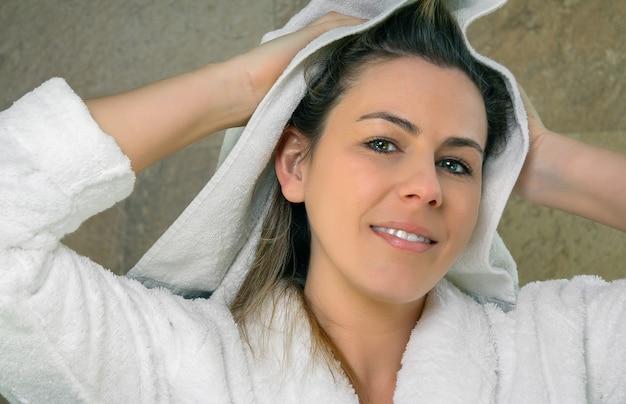 シャワーの後にタオルで彼女の濡れた髪を拭くバスローブと美しい若い女性のクローズアップ。健康と美容のコンセプト。