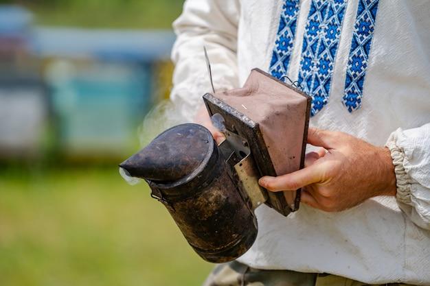 Крупный план курильщика пчелы в руках пчеловода на пасеке.
