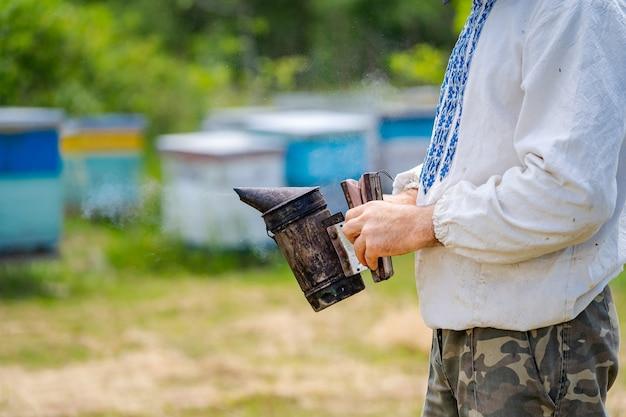 Крупный план курильщика пчелы в руках пчеловода на пасеке. Premium Фотографии