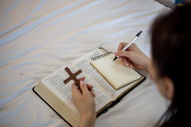 연필을 들고 성경과 여자 손을 클로즈업하고 무언가를 씁니다.