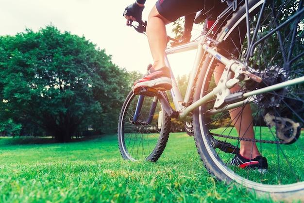 日没の公園で緑のフィールドに自転車の拡大写真。
