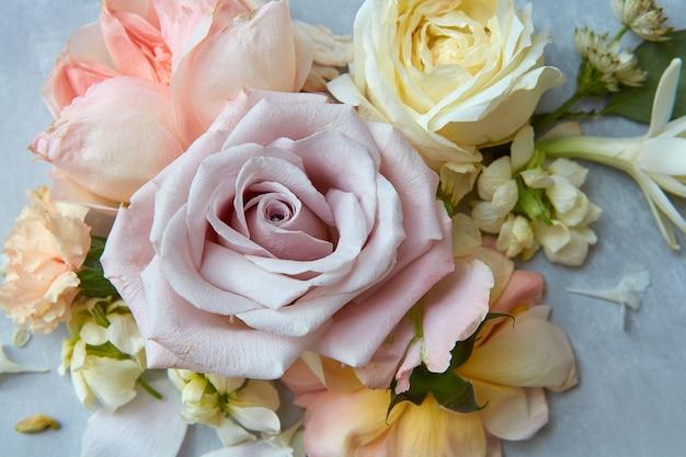 회색 배경에 표시되는 다른 꽃들 사이에서 큰 장미의 근접 촬영. 꽃의 구성은 발렌타인 데이의 모든 장식에 사용할 수 있습니다.