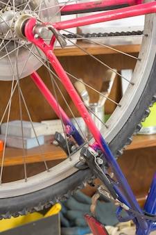 損傷した自転車の修復プロセスにおけるワークショップテーブル上の自転車ホイールのクローズアップ