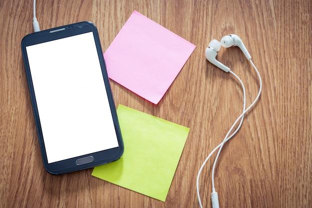 Макрофотография черный смартфон с белым экраном с наушниками