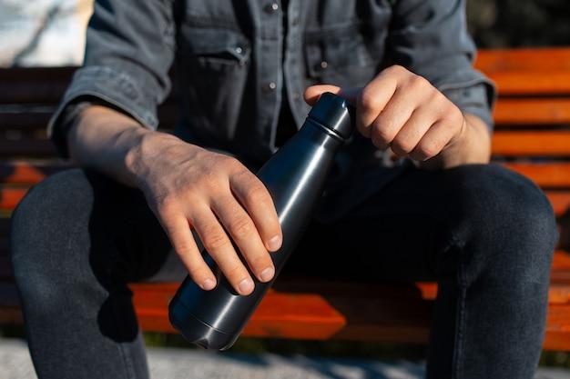 男性の手で黒い鋼のステンレス鋼の熱水ボトルのクローズアップ。再利用可能なボトルのコンセプト。ゼロウェイスト。