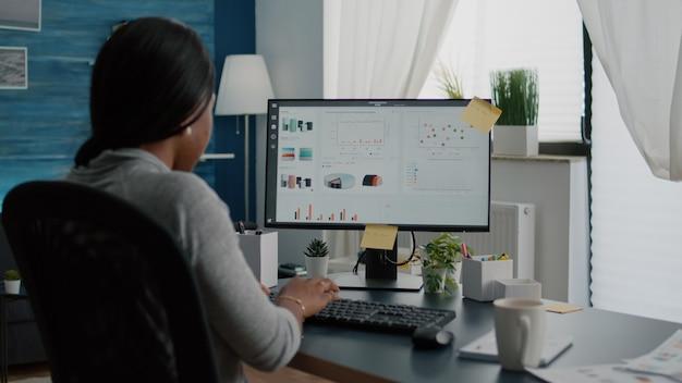Крупным планом черный студент просматривает финансовую инфографику и анализирует статистику на ноутбуке