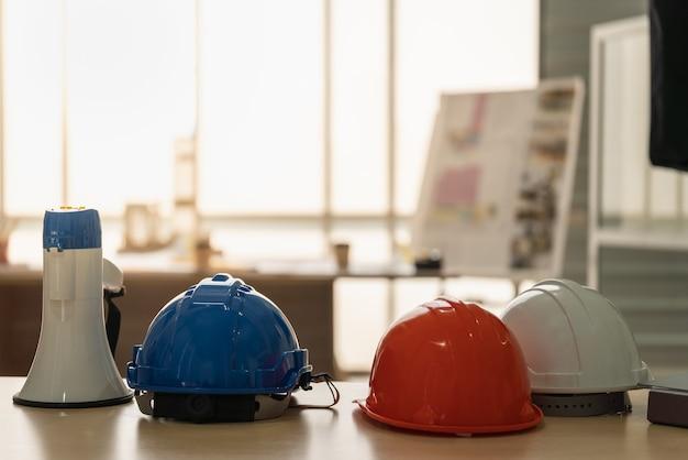 파란색, 주황색 및 흰색 하드 안전 헬멧 모자 엔지니어와 ãƒâƒã'â ãƒâ'ã'â¸ãƒâ'ã'â - 배경으로 건물 청사진과 나무 테이블에 egaphone의 근접 촬영.