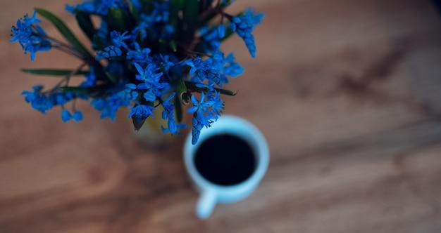 커피 컵 근처 나무 테이블에 파란색 제비 꽃의 근접 촬영.