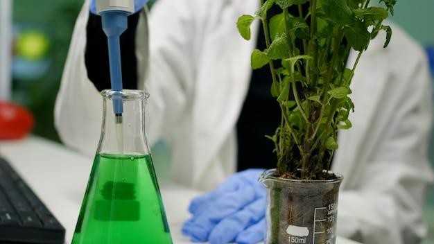 遺伝的液体を取るためにマイクロピペットを使用して植物学者の女性のクローズアップ
