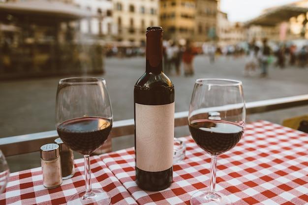 Крупным планом бутылка красного вина и бокалы на столе ресторана на фоне площади синьории в летний день