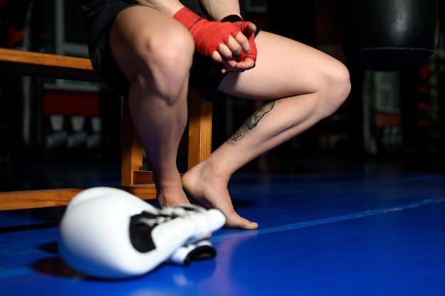 Крупным планом ноги боксера, отдыхая на скамейке в тренажерном зале после тренировки.