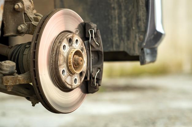 새로운 타이어 교체 과정에서 수리를 위해 브레이크 캘리퍼가있는 차량의 브레이크 디스크의 근접 촬영.
