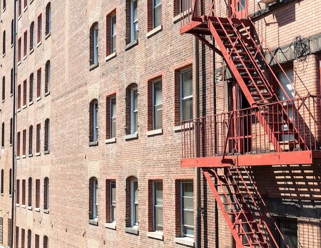 Крупный план кирпичного здания с пожарными лестницами.