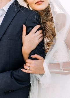 婚約指輪を身に着けて、新郎を抱き締める花嫁のクローズアップ