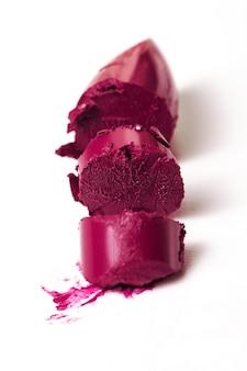 壊れた美しい紫色の口紅の拡大写真。ファッション。明るい背景。