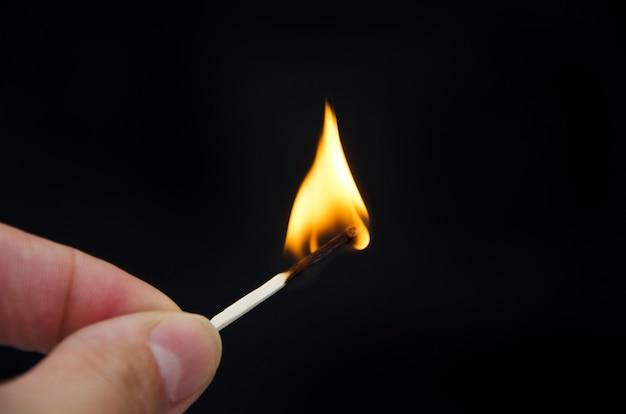 黒の手で燃える試合のクローズアップ。