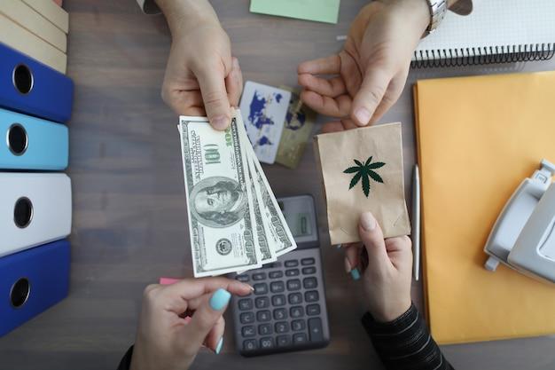 Крупный план горящего пакета марихуаны за наличные доллары.