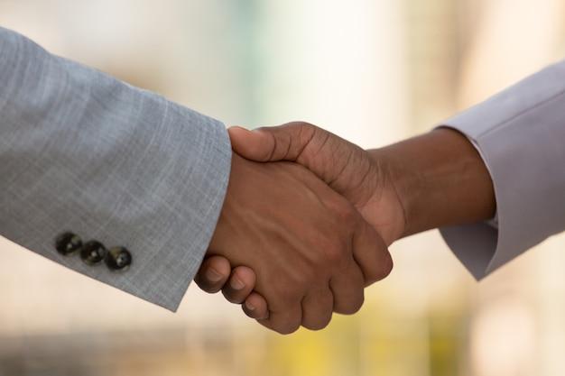 ビジネス部門の同僚の握手のクローズアップ