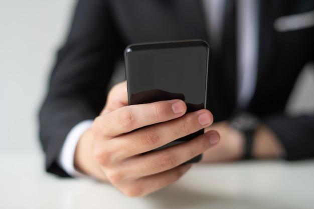 잡고 스마트 폰을 사용 하여 비즈니스 맨의 근접 촬영
