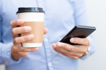 Closeup of business man holding smartphone and drink