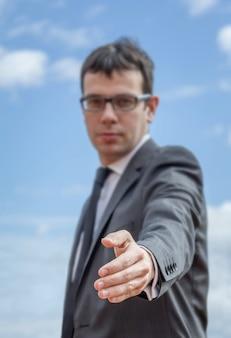 契約を結ぶ準備ができている彼の開いた手を示すビジネスマンのクローズアップ