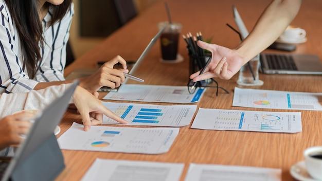 서류를 가리키는 여성과 함께 프로젝트에 대해 논의하는 비즈니스 사람들의 근접 촬영
