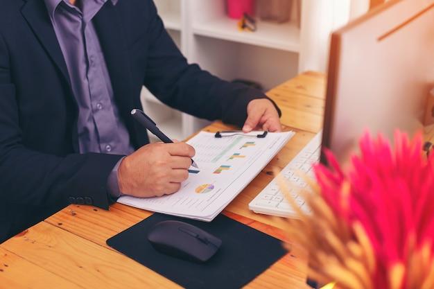 綿密な事業計画のためにシートやコンピュータからのデータを見ているはずのビジネスマンのクローズアップ。