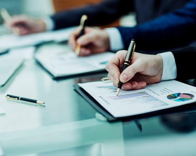 Крупным планом бизнес-команда работает с финансовыми диаграммами