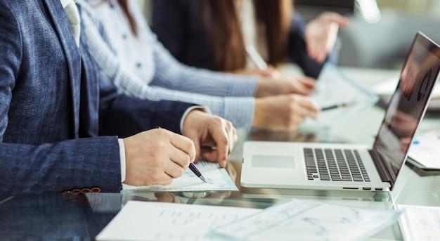 Крупным планом бизнес-группа работает с финансовыми документами на рабочем месте в офисе.