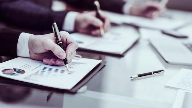 ビジネスチームのクローズアップは、オフィスの職場で財務スケジュールを処理しています