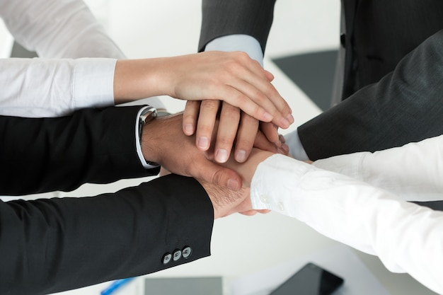 서로의 위에 함께 그들의 손을 댔을 단결을 보여주는 비즈니스 팀의 근접 촬영. 팀워크의 개념입니다.
