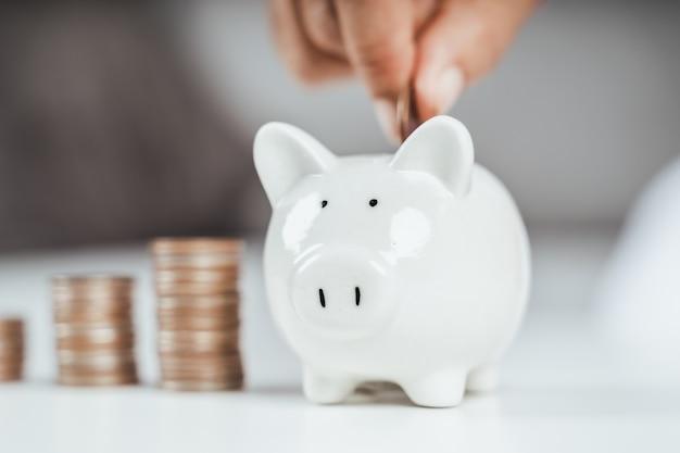 お金を節約するために貯金箱にお金のコインを入れているビジネス女性の手のクローズアップ。お金と財務の概念を節約する