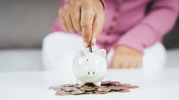 돈을 절약하기 위해 돼지 저금통에 돈 동전을 넣어 비즈니스 여자 손의 근접 촬영. 돈과 금융 개념을 절약