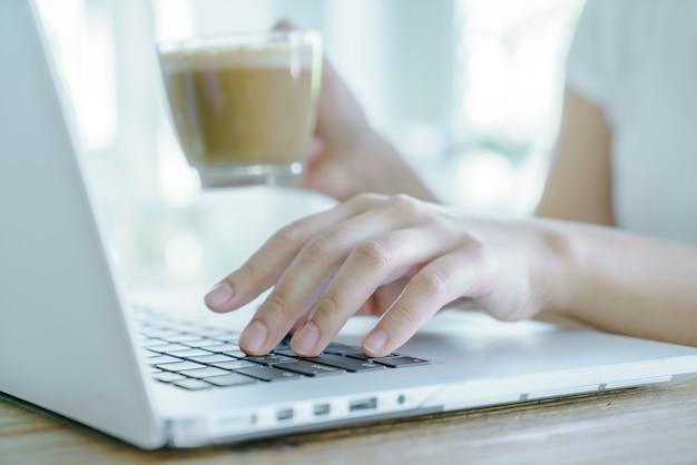 Крупным планом деловая женщина, руки, набрав на клавиатуре ноутбука и cof