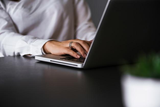 ノートパソコンのキーボードで入力するビジネス女性の手のクローズアップ