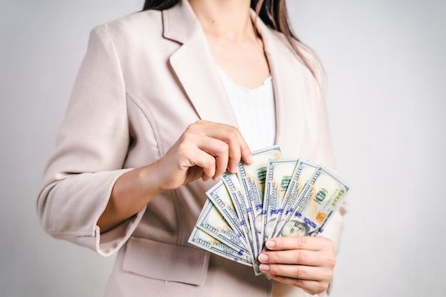 ビジネスの女性のクローズアップは私たちにお金を数える私たち白のドル札を手します。お金の概念。
