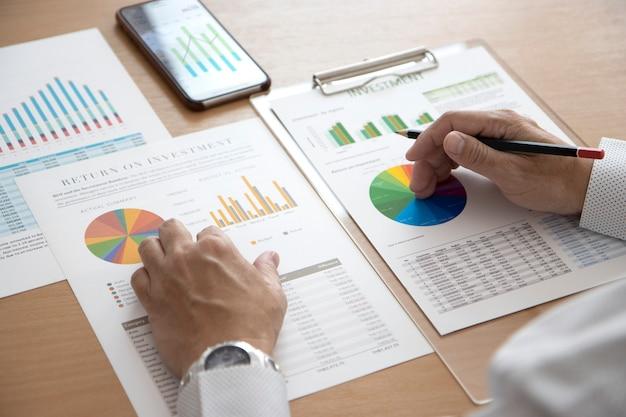 Крупный план руки бизнесмена, держащего карандаш, просматривая финансовую отчетность на предмет эффективности бизнеса или рентабельности инвестиций
