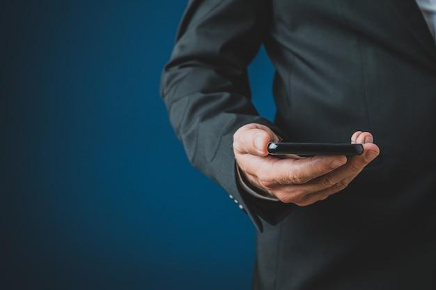 그의 손에 스마트 휴대 전화를 들고 소송에서 사업가의 근접 촬영. 해군 파란색 배경 위에.