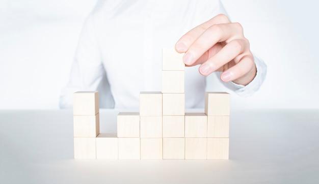 空の木製の立方体でピラミッドを作るビジネスマンのクローズアップ。ビジネス階層と人的資源の概念。