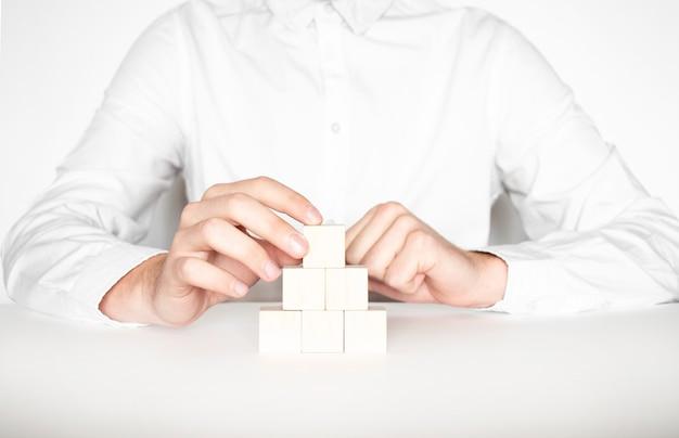 空の木製の立方体でピラミッドを作るビジネスマンのクローズアップ。