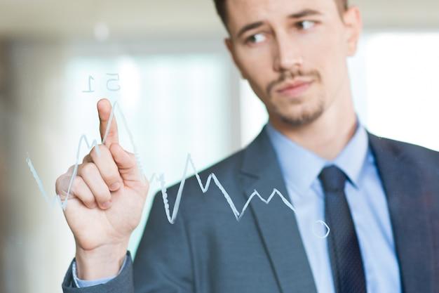 ガラス上のグラフにポインティングビジネスマンのクローズアップ
